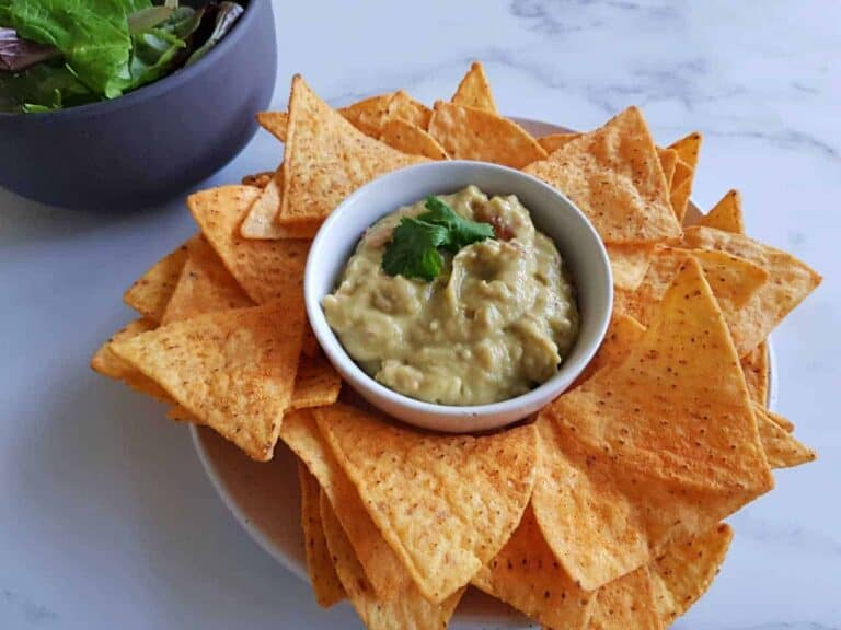 Creamy guacamole on a plate of nachos on a marble table.