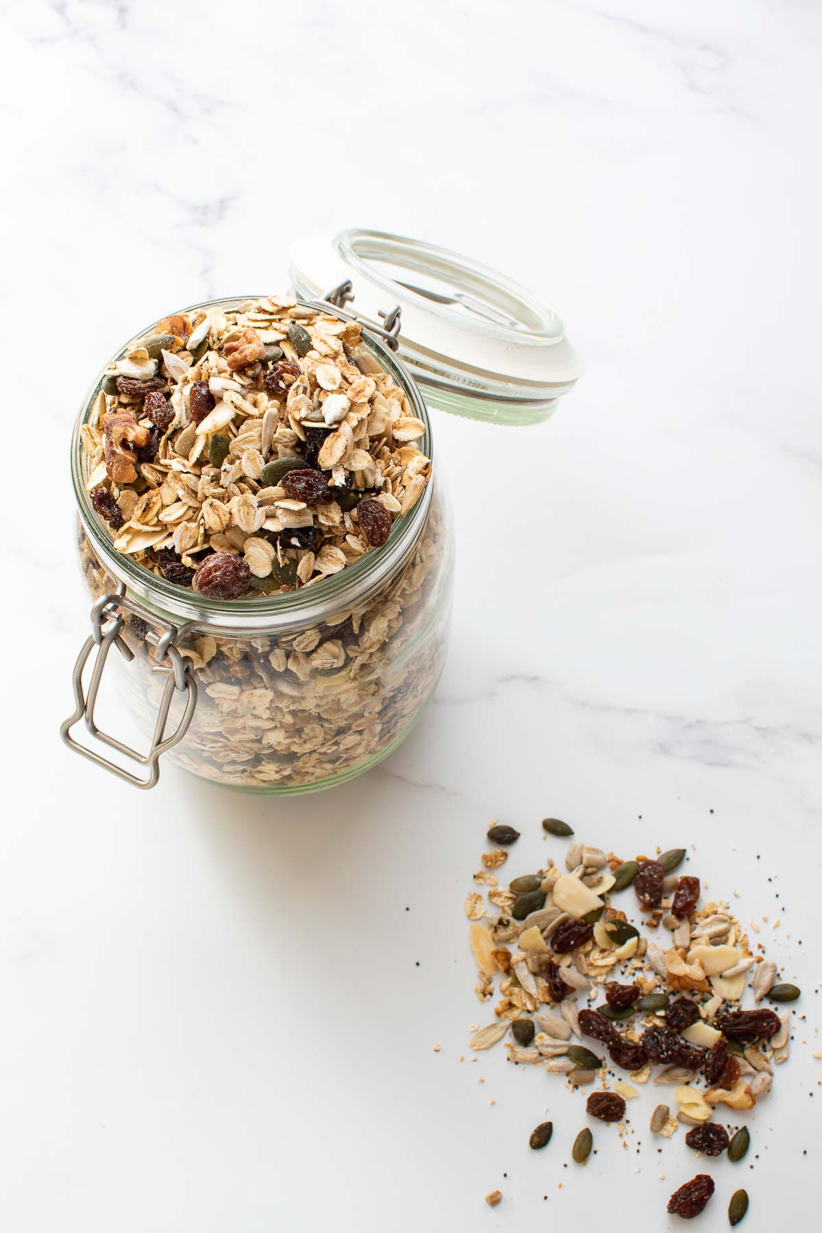 Muesli in a jar, with some muesli scattered around on a marble table.