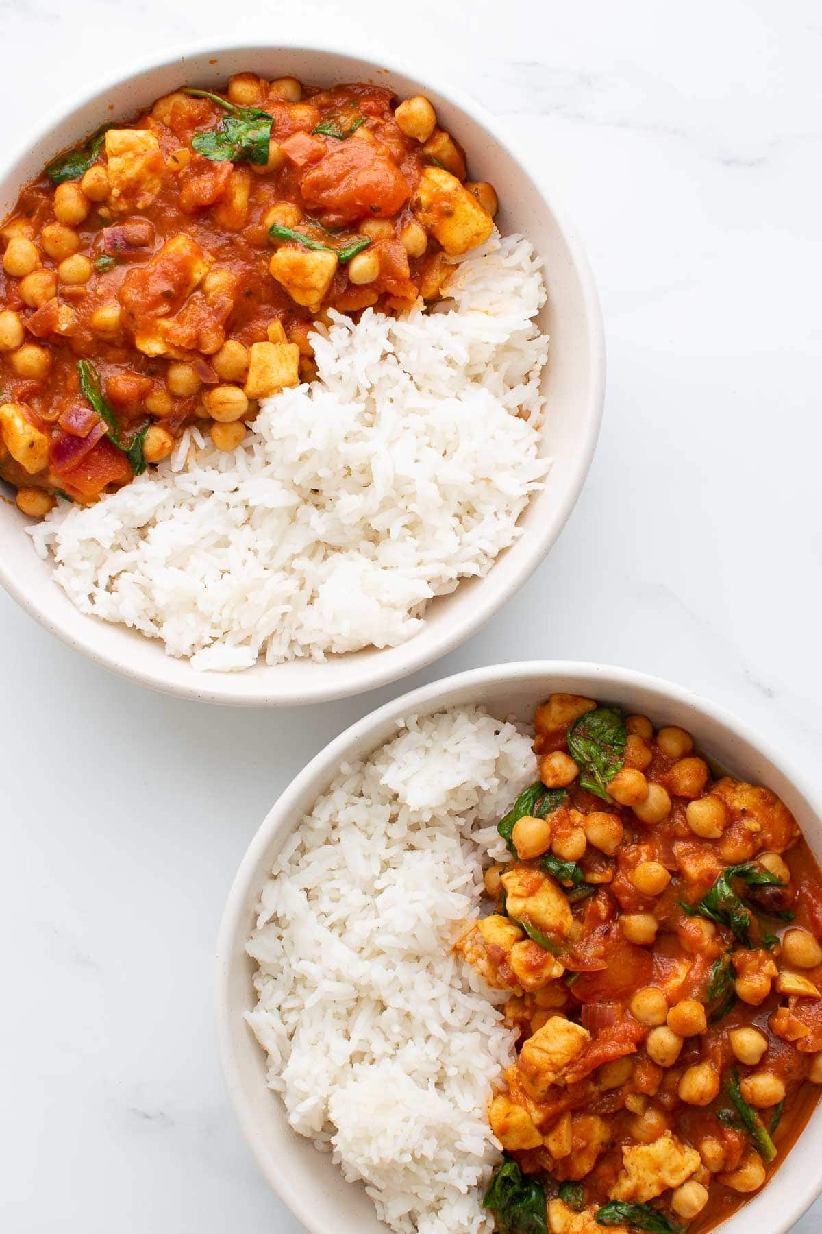 Two bowls of chickpea curry with rice.