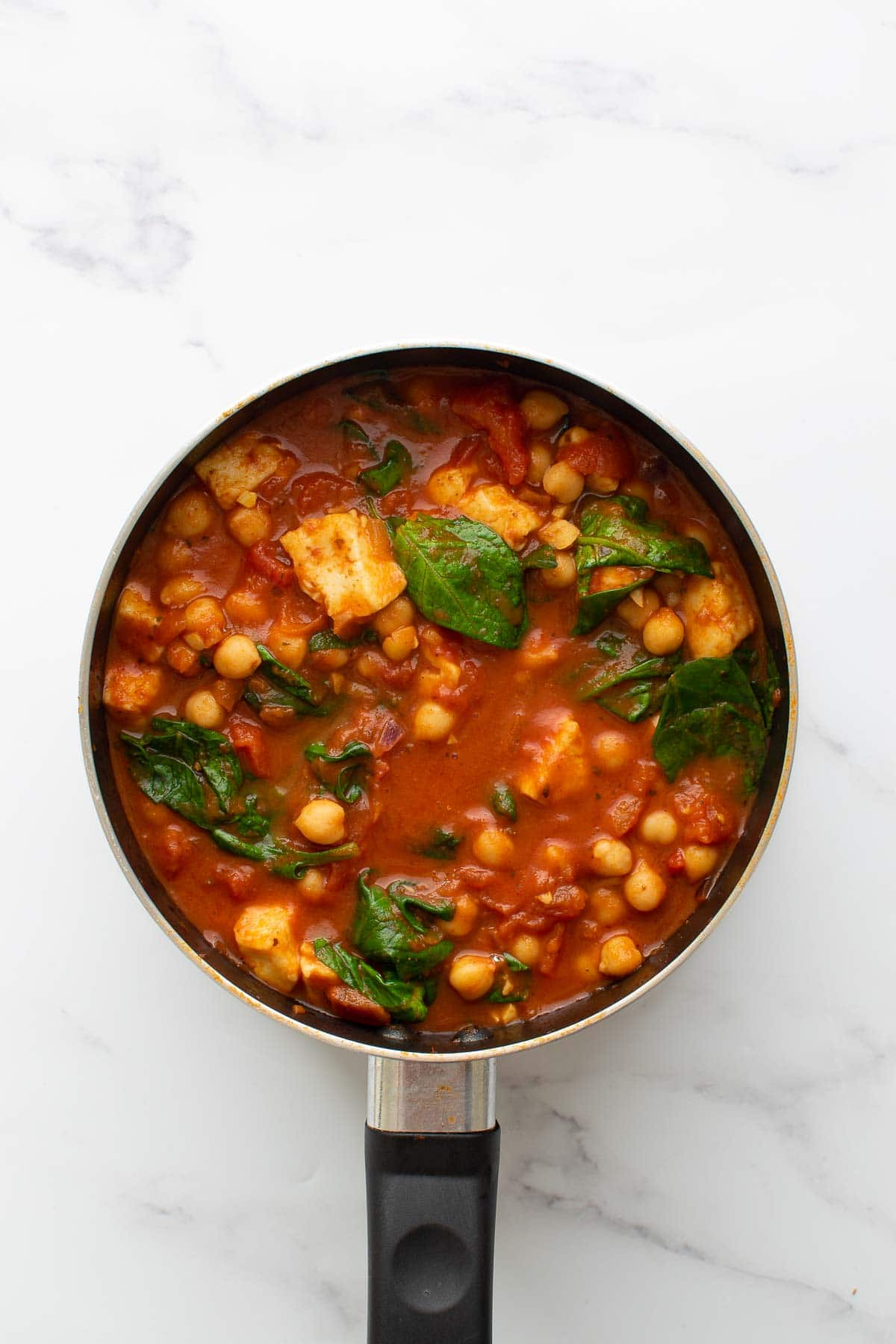 Halloumi and spinach curry in a pot.
