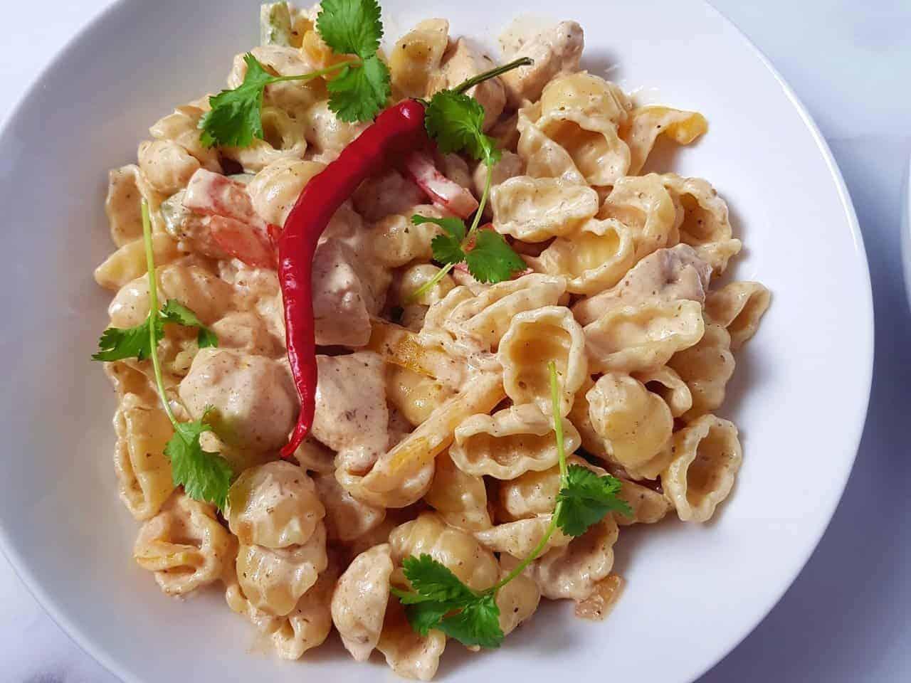 A bowl of creamy fajita pasta, decorated with chili and coriander.