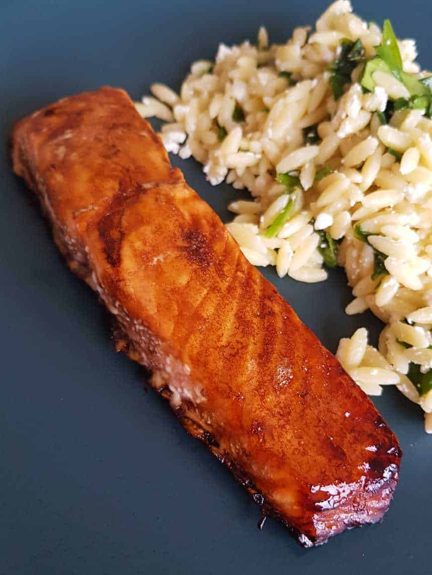 Balsamic and maple glazed salmon on a blue plate with salad in the background.