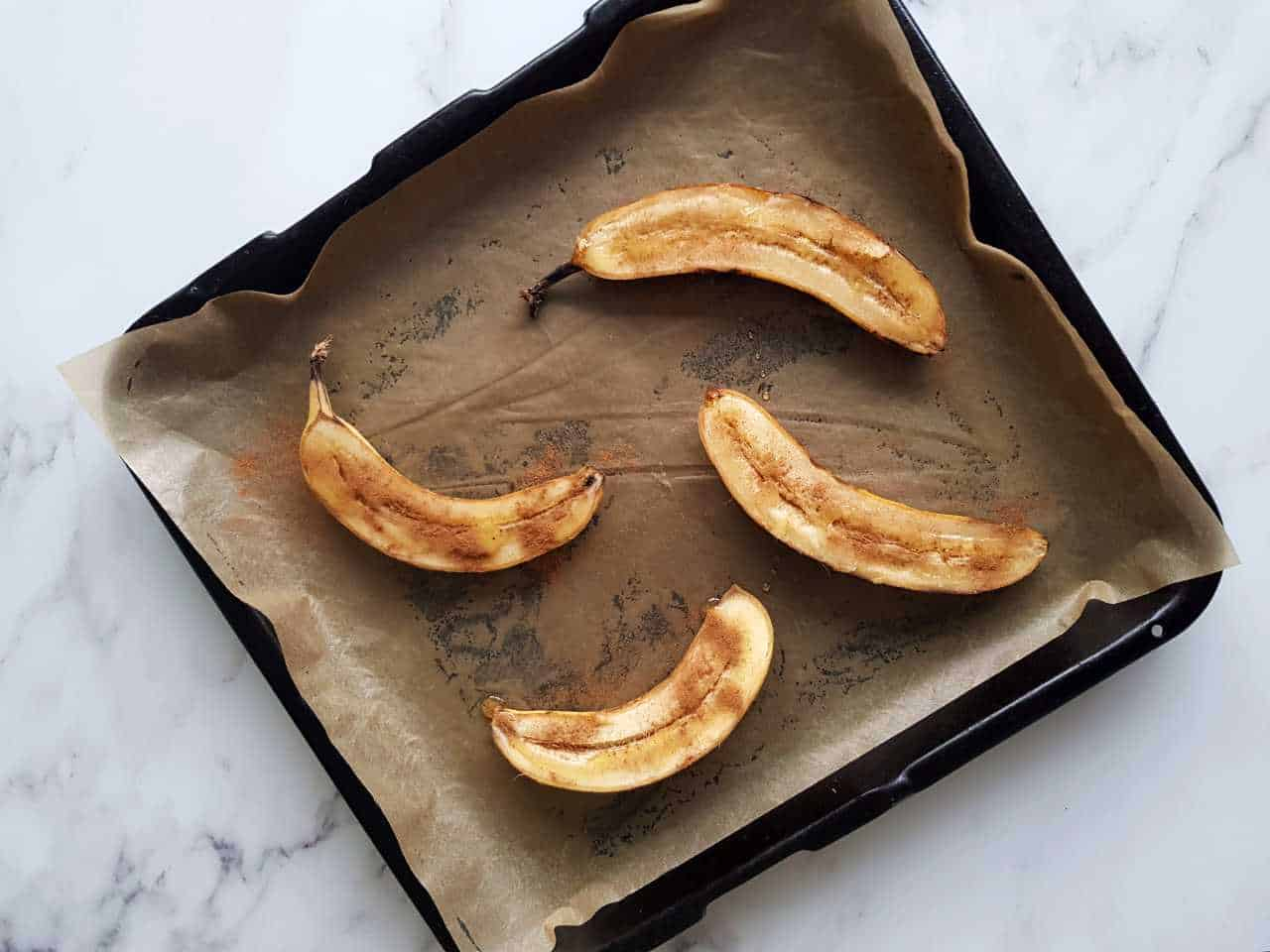 Sliced oven baked bananas on a baking sheet ready to bake on a marble table.
