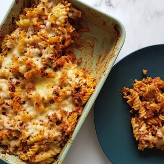 Beef pasta bake in a casserole dish with a plated portion on the side, on a marble table.