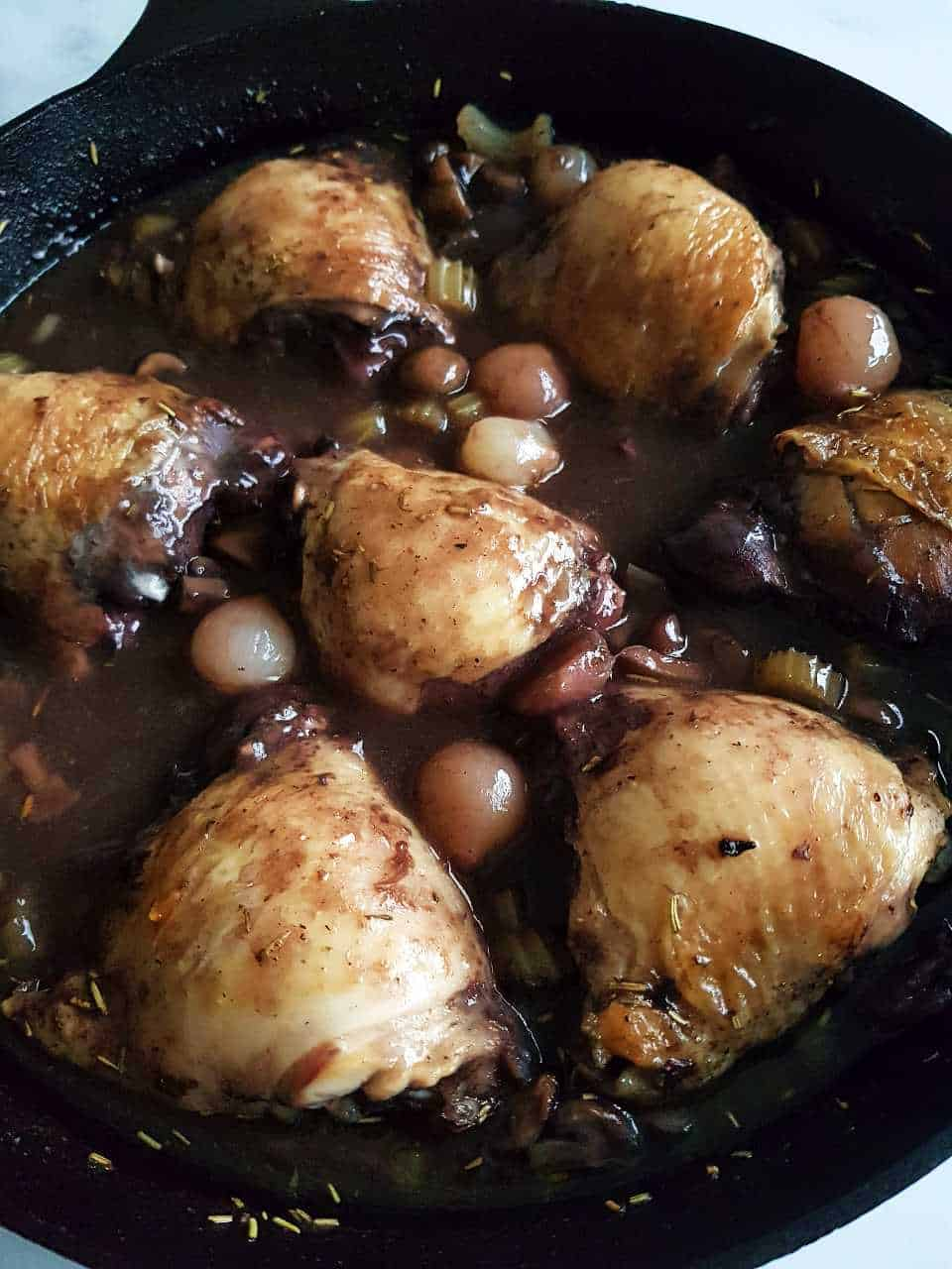 Coq au vin in a cast iron pan.