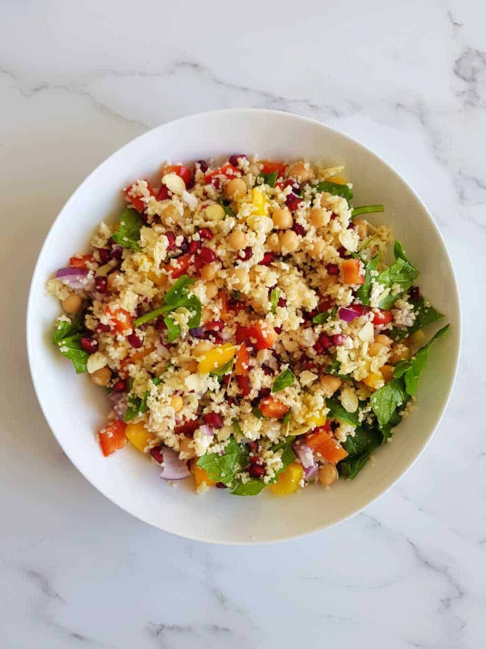 Couscous salad with pomegranate in a white bowl on a marble table