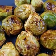 Roasted brussel sprouts with honey and sriracha on a dark plate.