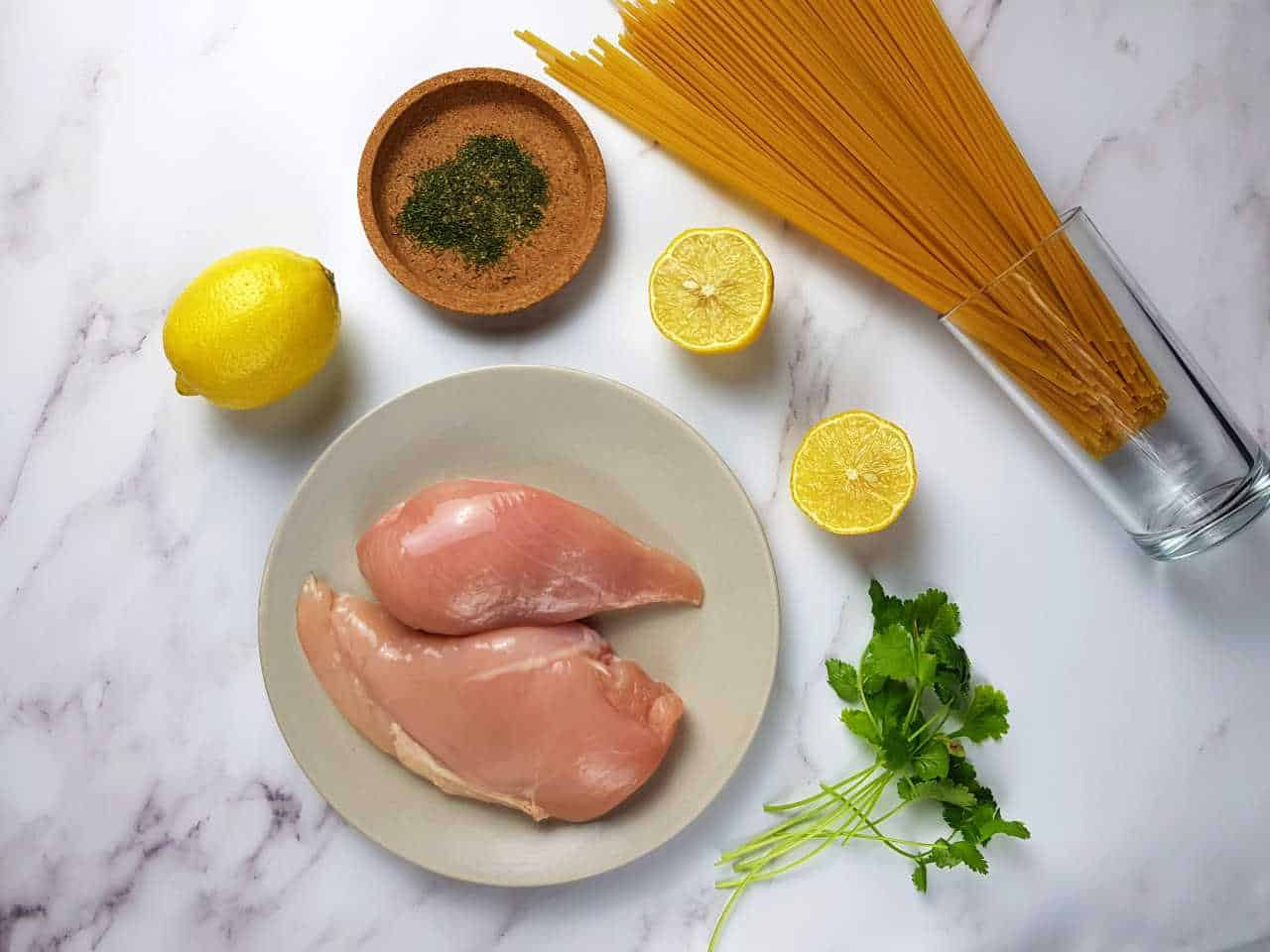 Chicken fillets, dill, lemon, coriander and pasta laid down on a marble table.