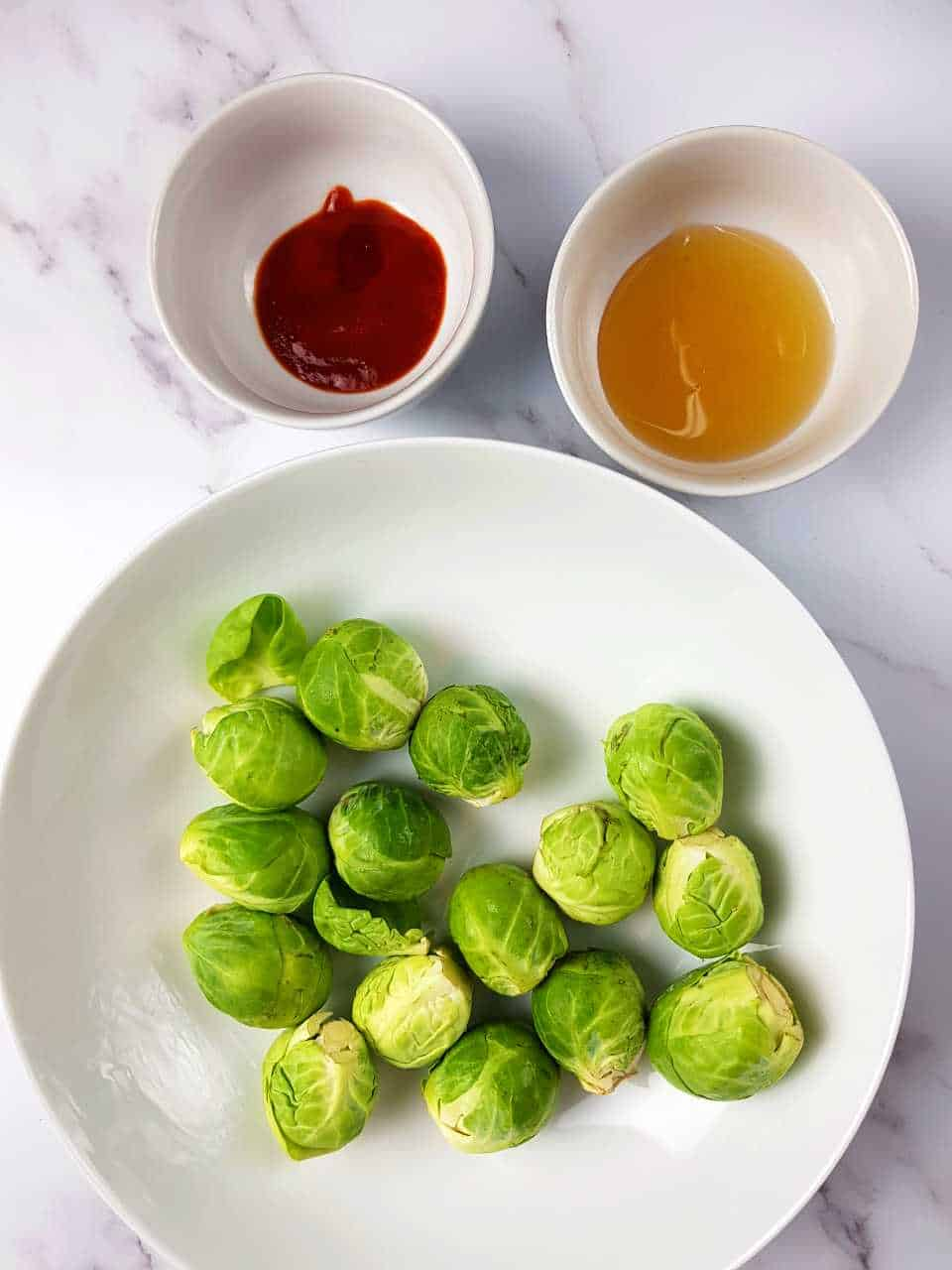 Brussels sprouts on a white plate with bowls of honey and sriracha in the background.