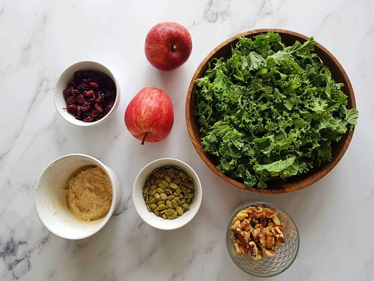 All ingredients for kale salad with apples laid out in small bowls on a marble table.