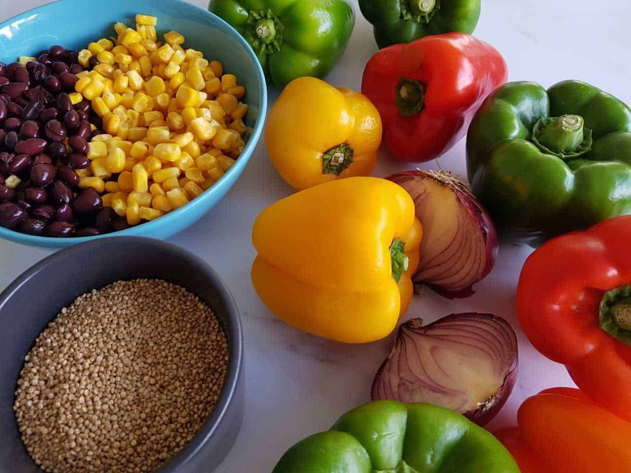 All the ingredients for stuffed peppers with quinoa and black beans laid out on a marble table.