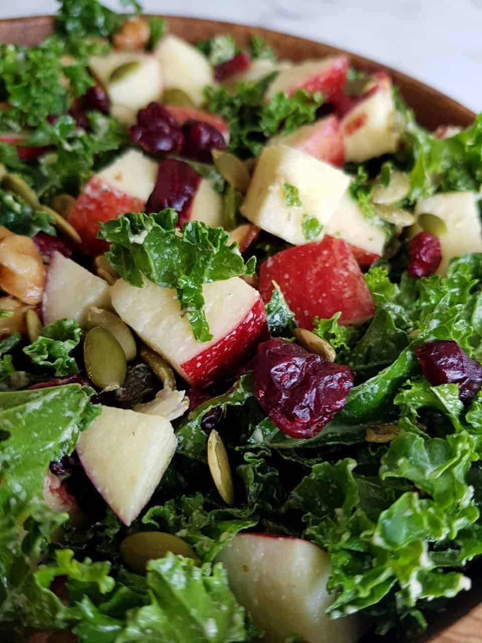 Kale and apple salad in a wooden bowl.