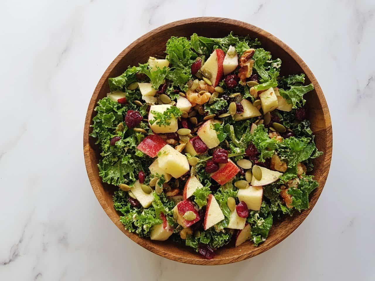 Kale salad with apples in a wooden bowl on a marble table.