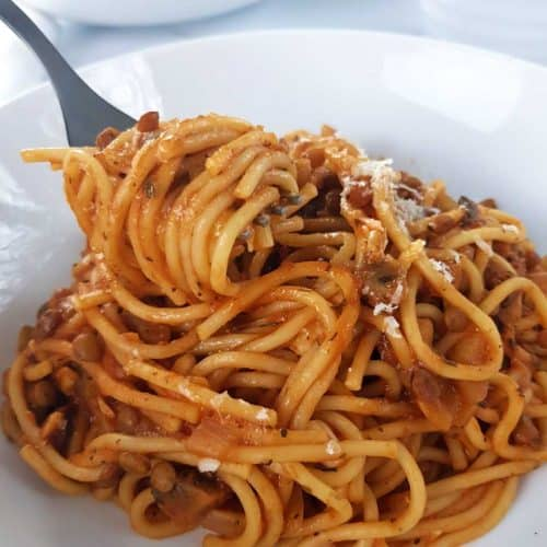 Lentil and mushroom bolognese on a white plate, with a fork lifting it up.