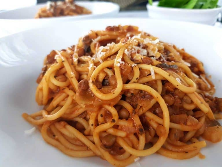 Lentil and mushroom bolognese on a white plate.