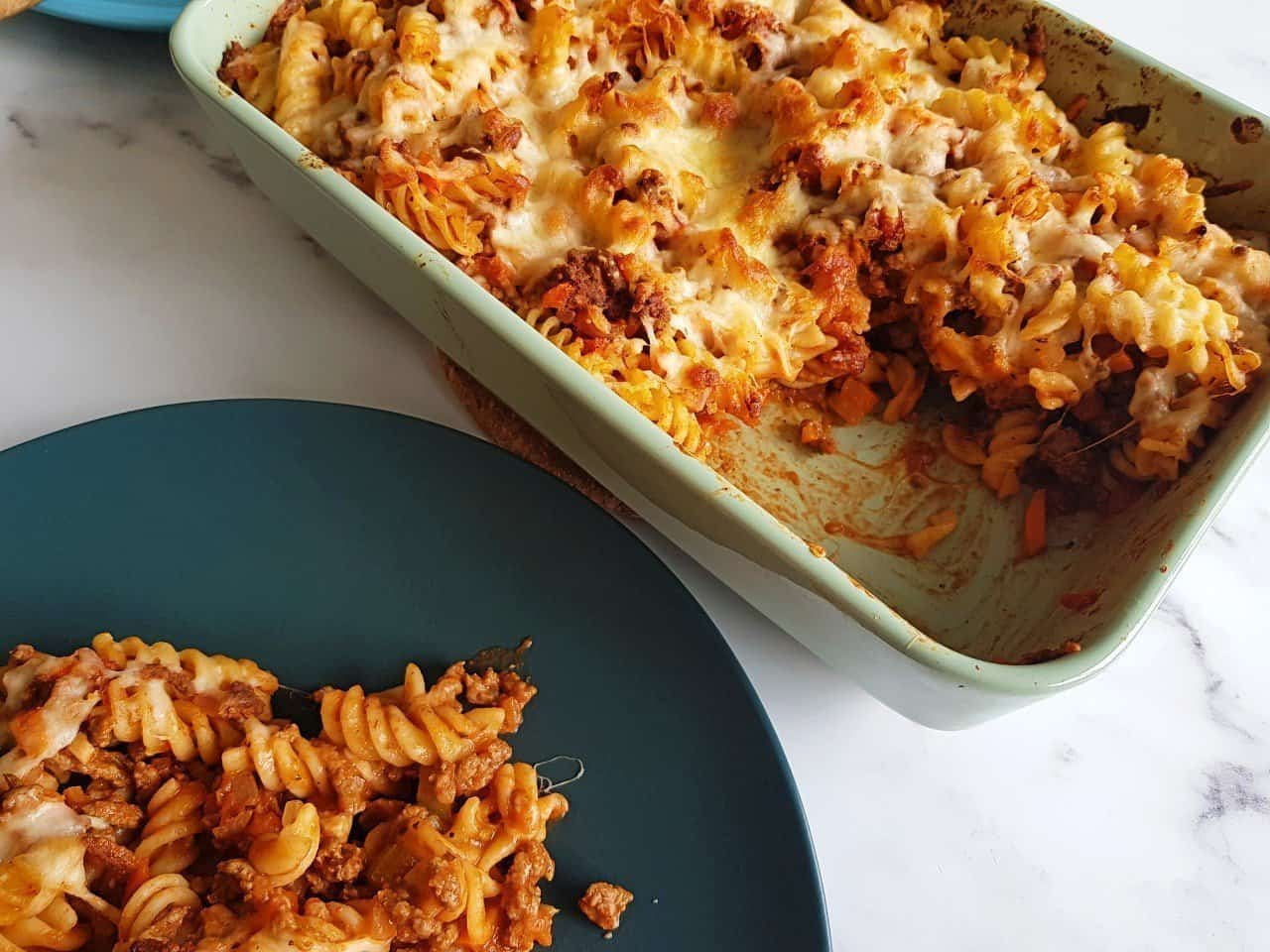 Minced beef pasta bake with a plated portion in front.