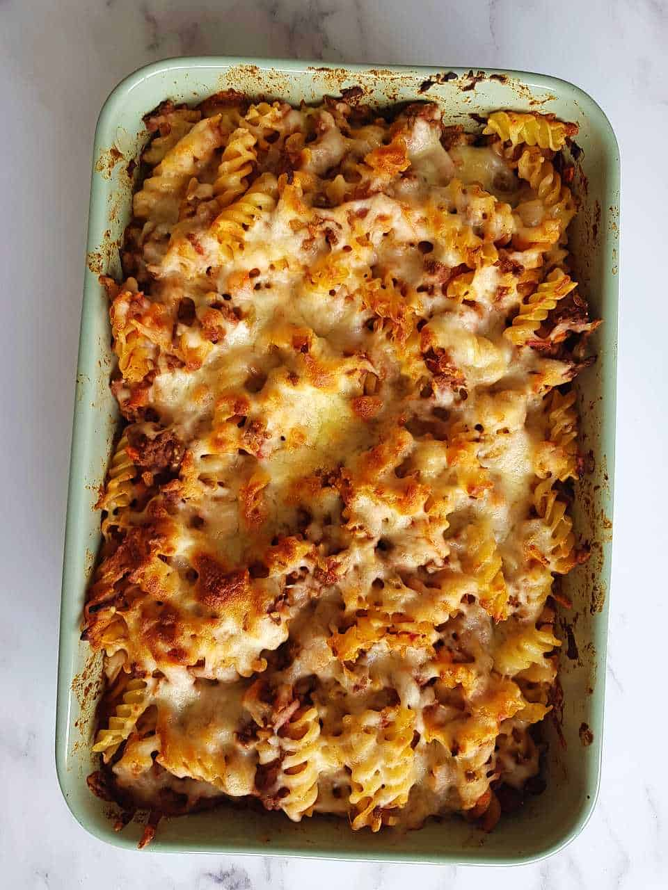 Minced beef pasta bake in a casserole dish on a marble table.
