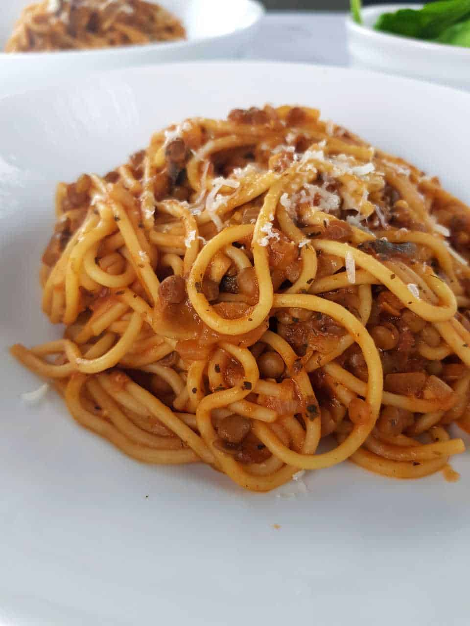 Mushroom and lentil bolognese on a white plate.