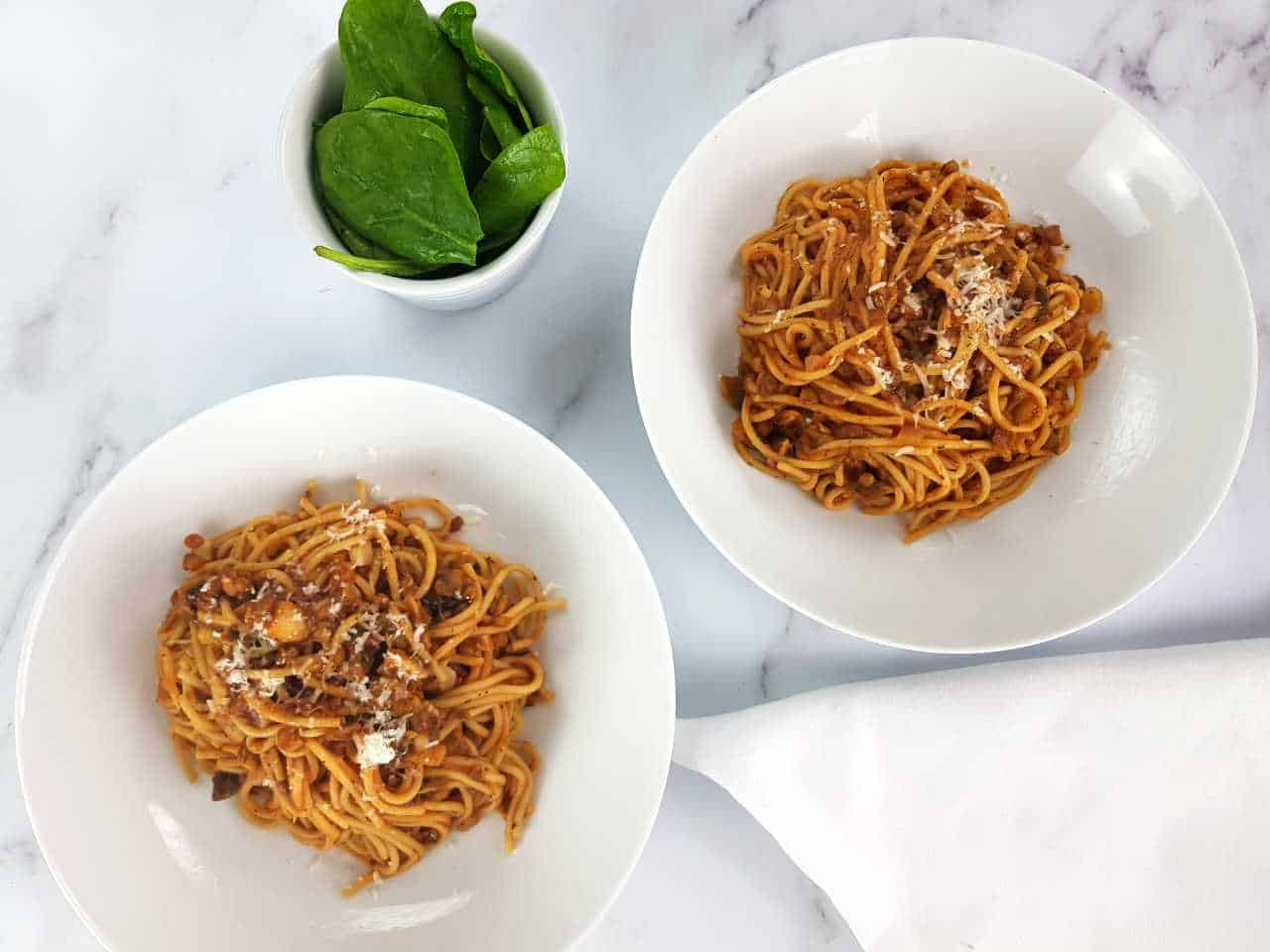 Mushroom and lentil bolognese in white pasta bowls with a bowl of spinach and a white napkin on a marble table.
