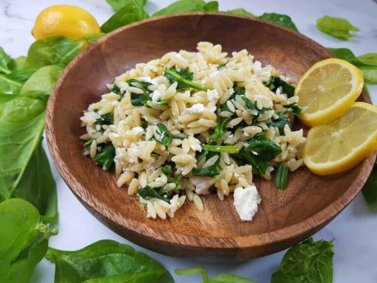 Orzo salad in a wooden bowl with lemon slices on the side.