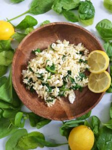 Orzo salad in a wooden bowl, surrounded by lemons and spinach leaves.