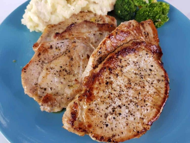 Pork loin steaks on a blue plate with mashed potatoes and broccoli.
