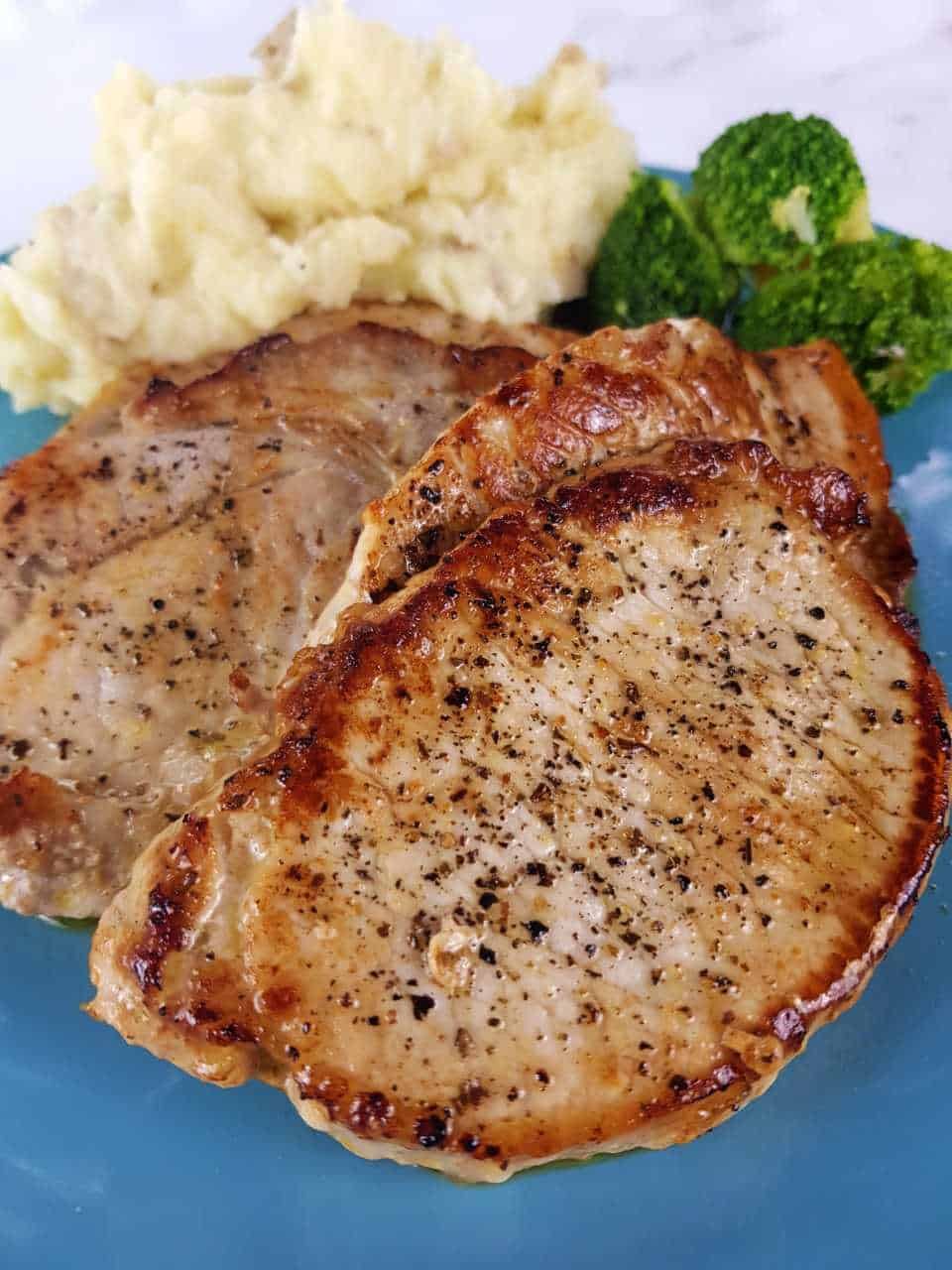 Pork steaks on a blue plate with mashed potatoes and broccoli.