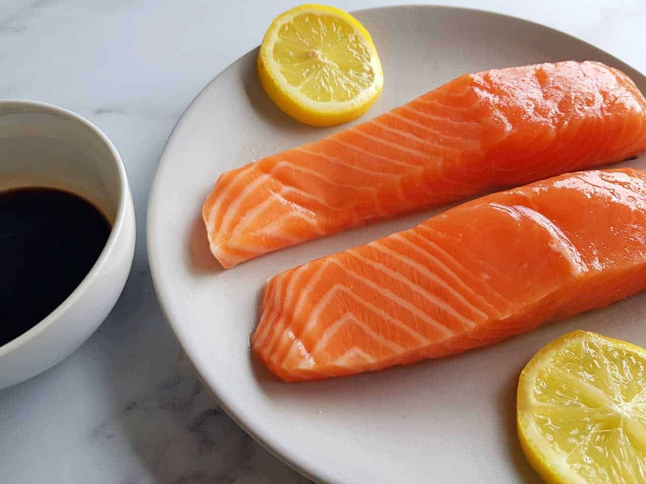 Raw salmon fillet on a plate with lemon slices, and a bowl of balsamic maple glaze.
