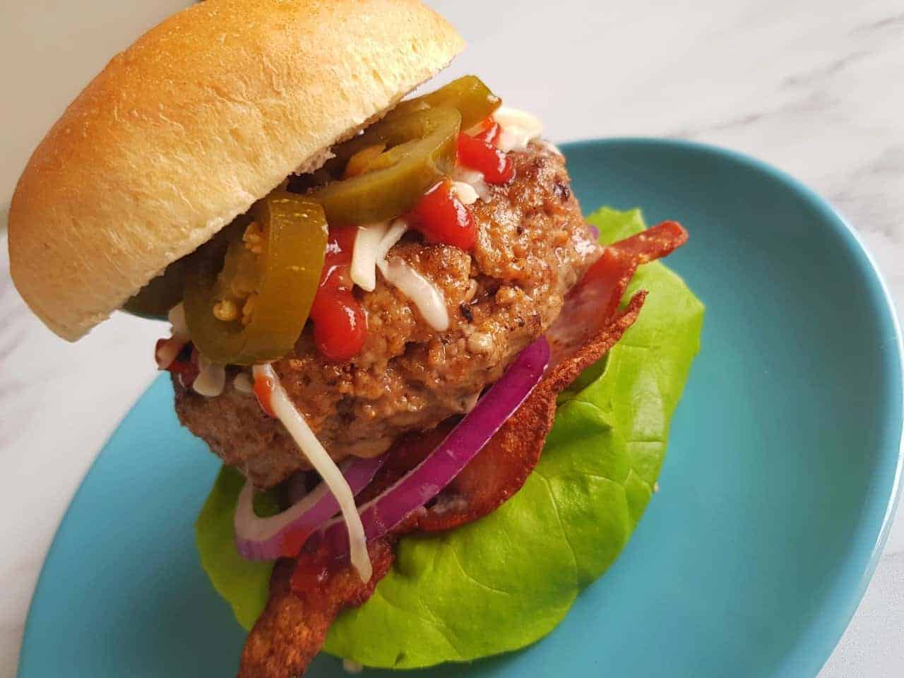 A delicious spicy beef burger on a blue plate.