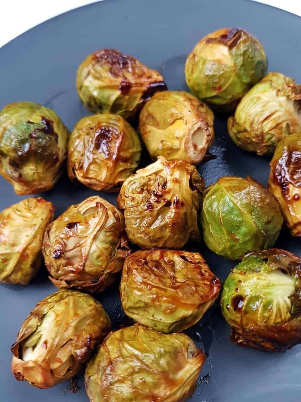 Oven roasted honey and sriracha brussels sprouts on a grey plate.