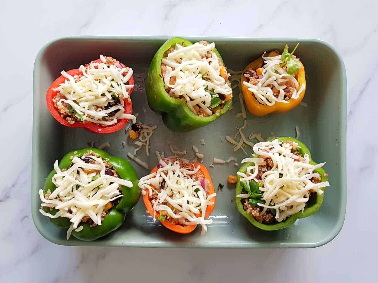 Uncooked stuffed peppers in an oven dish.