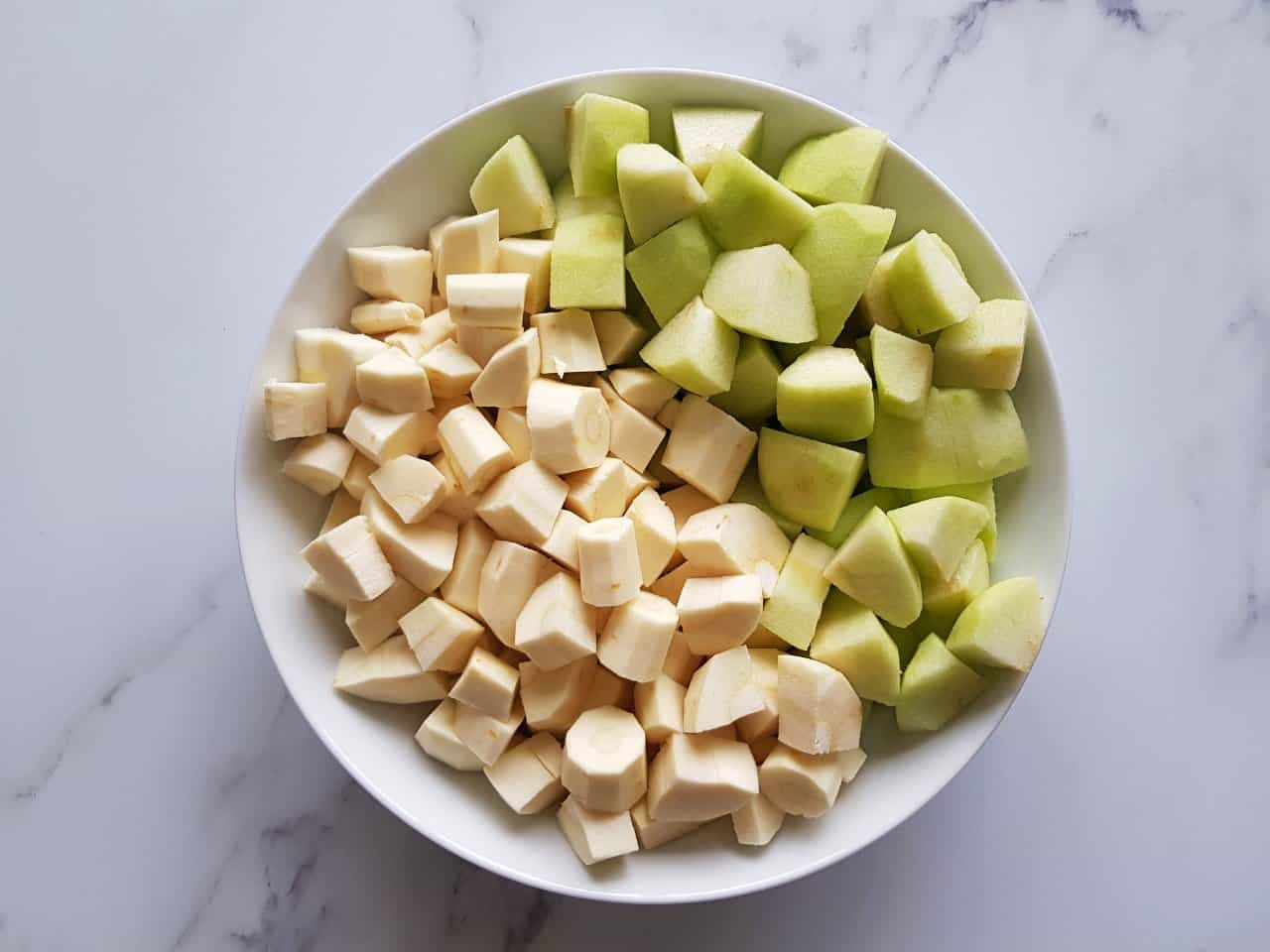 Diced parsnips and apples in a white bowl sat on a table.