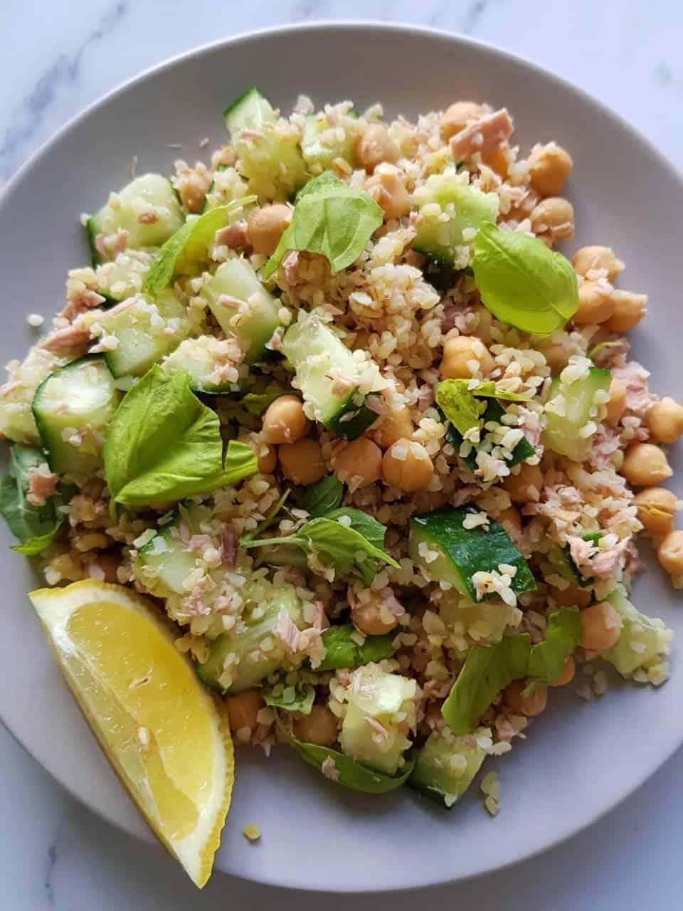 Tuna bulgur salad on a plate with a slice of lemon on the side.