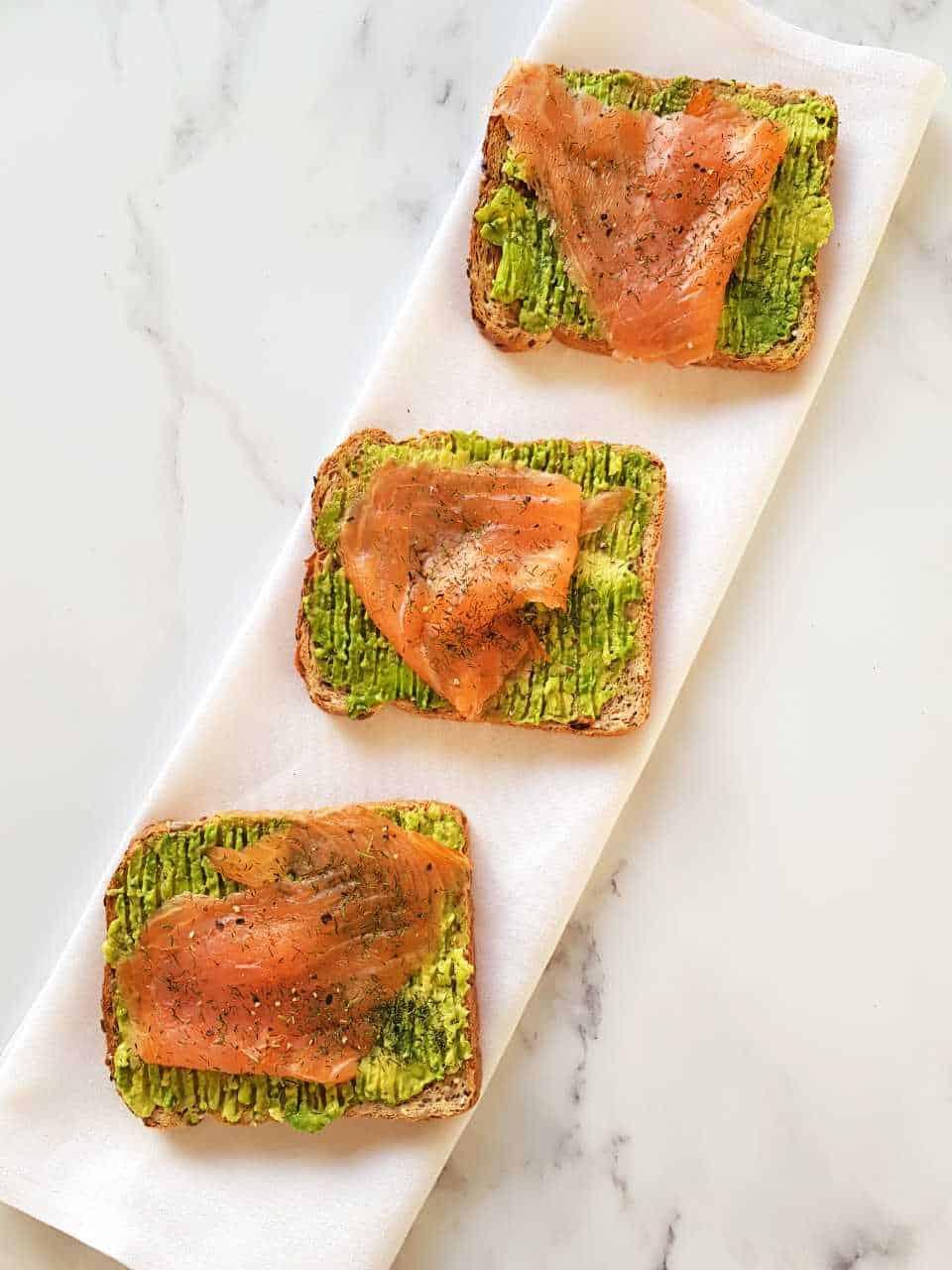 Avocado toast with smoked salmon on a white napkin on a marble table.