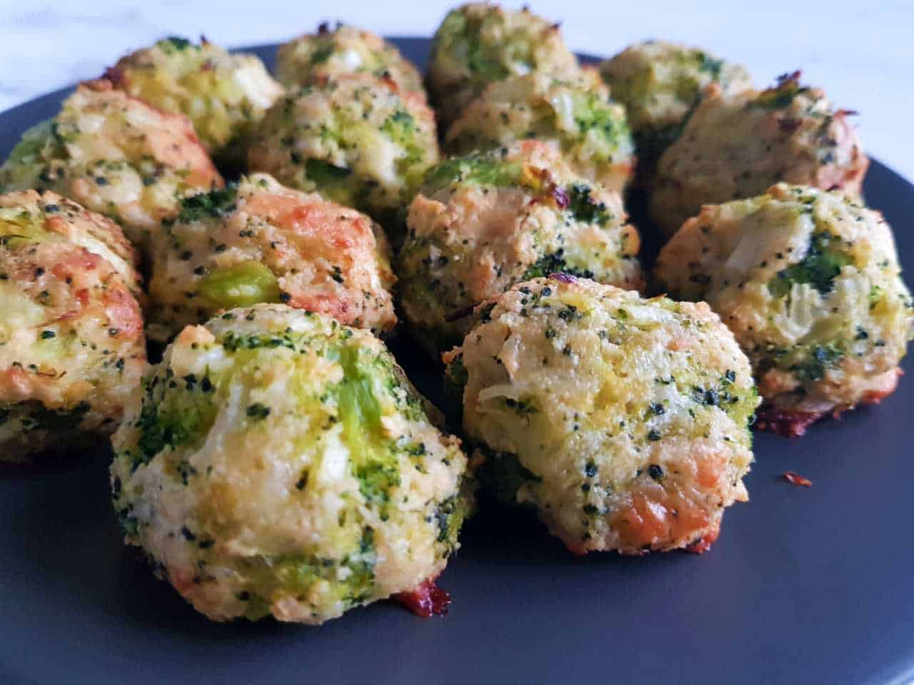 Broccoli and cheese balls on a gray plate.