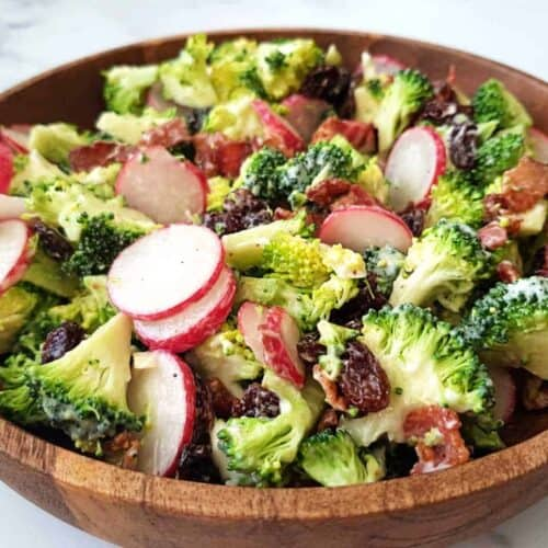 Broccoli salad with raisins and bacon in a wooden bowl.
