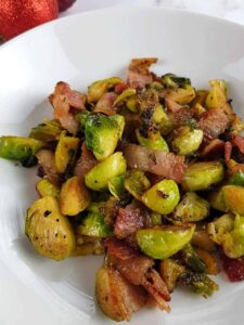 Brussels sprouts and bacon on a white plate.