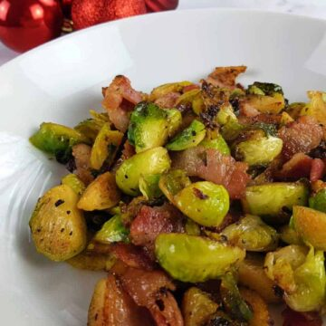 Brussels sprouts with bacon on a white plate with red baubles in the background.