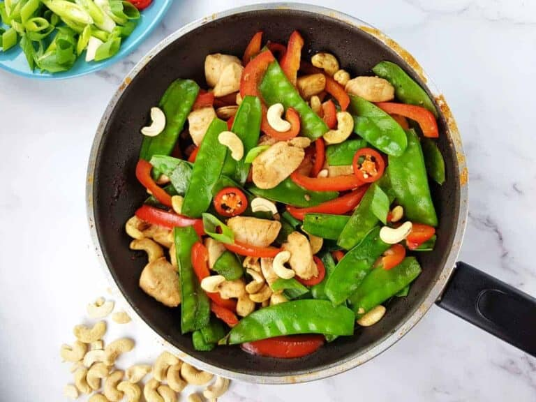 Cashew chicken stir fry in a frying pan on a marble table.