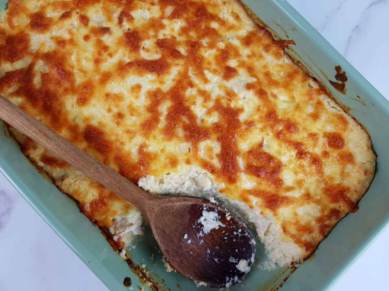 Cauliflower rice and chicken casserole in a blue casserole dish with a wooden spoon.