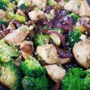 Chicken and broccoli stir fry in a black pan.