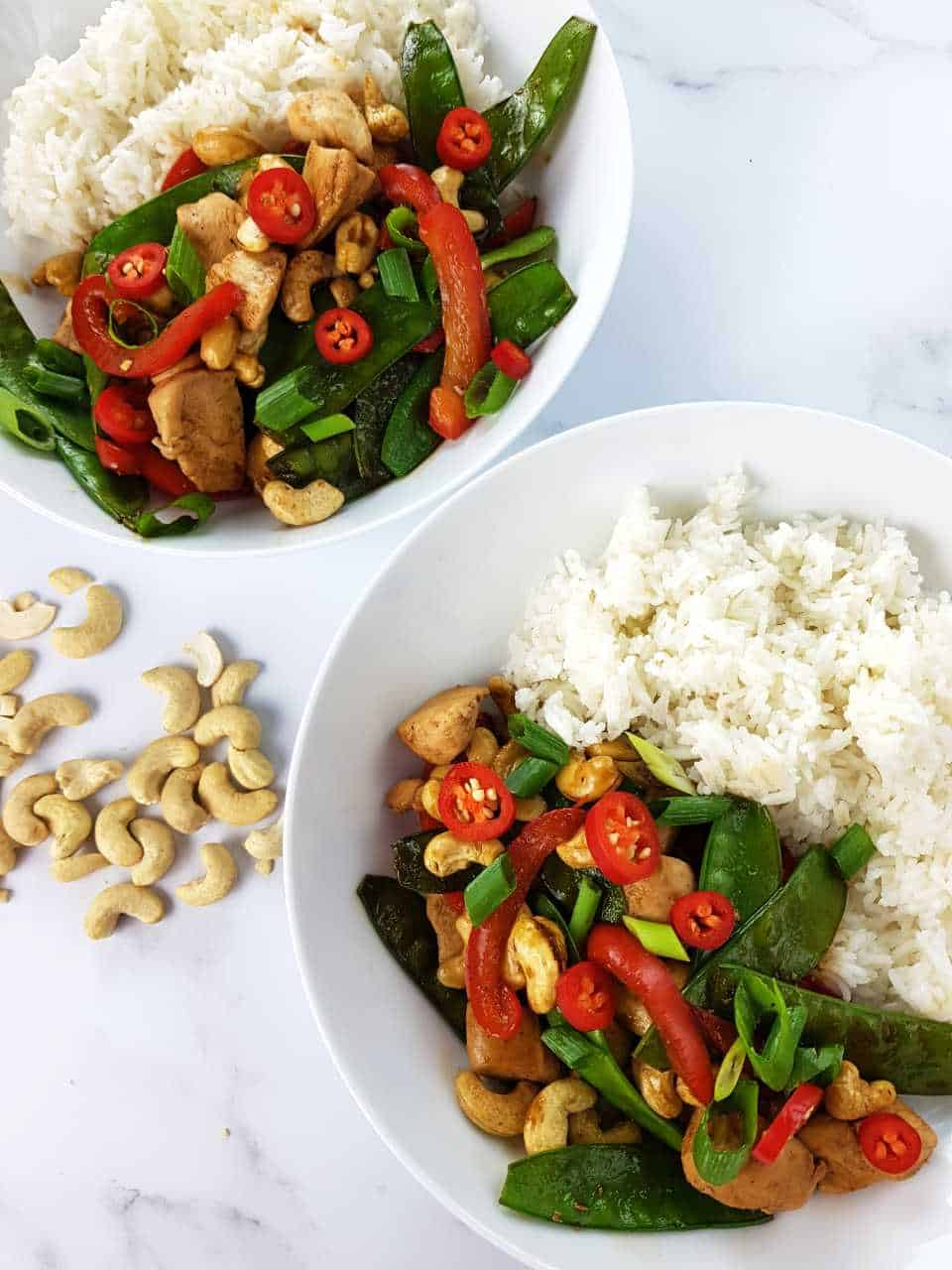 Chicken and cashew stir fry with rice in white bowls on a marble table.
