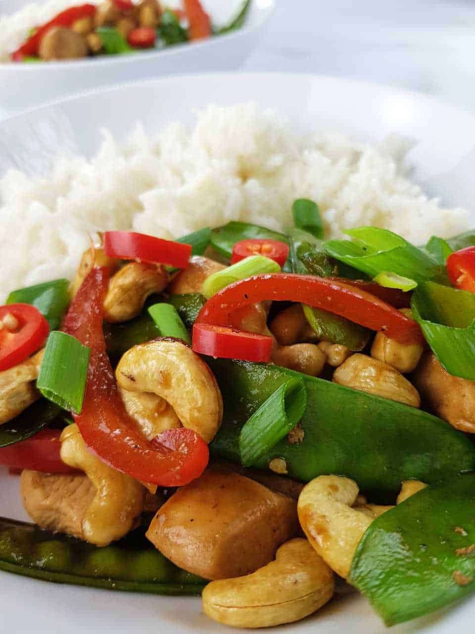 Chicken stir fry with cashews and rice in white bowls on a marble table.