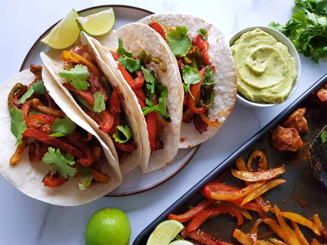 Plated fajitas with guacamole and lime on the side.