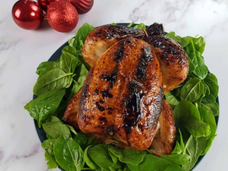 Honey roast chicken on a bed of spinach with red baubles in the background.