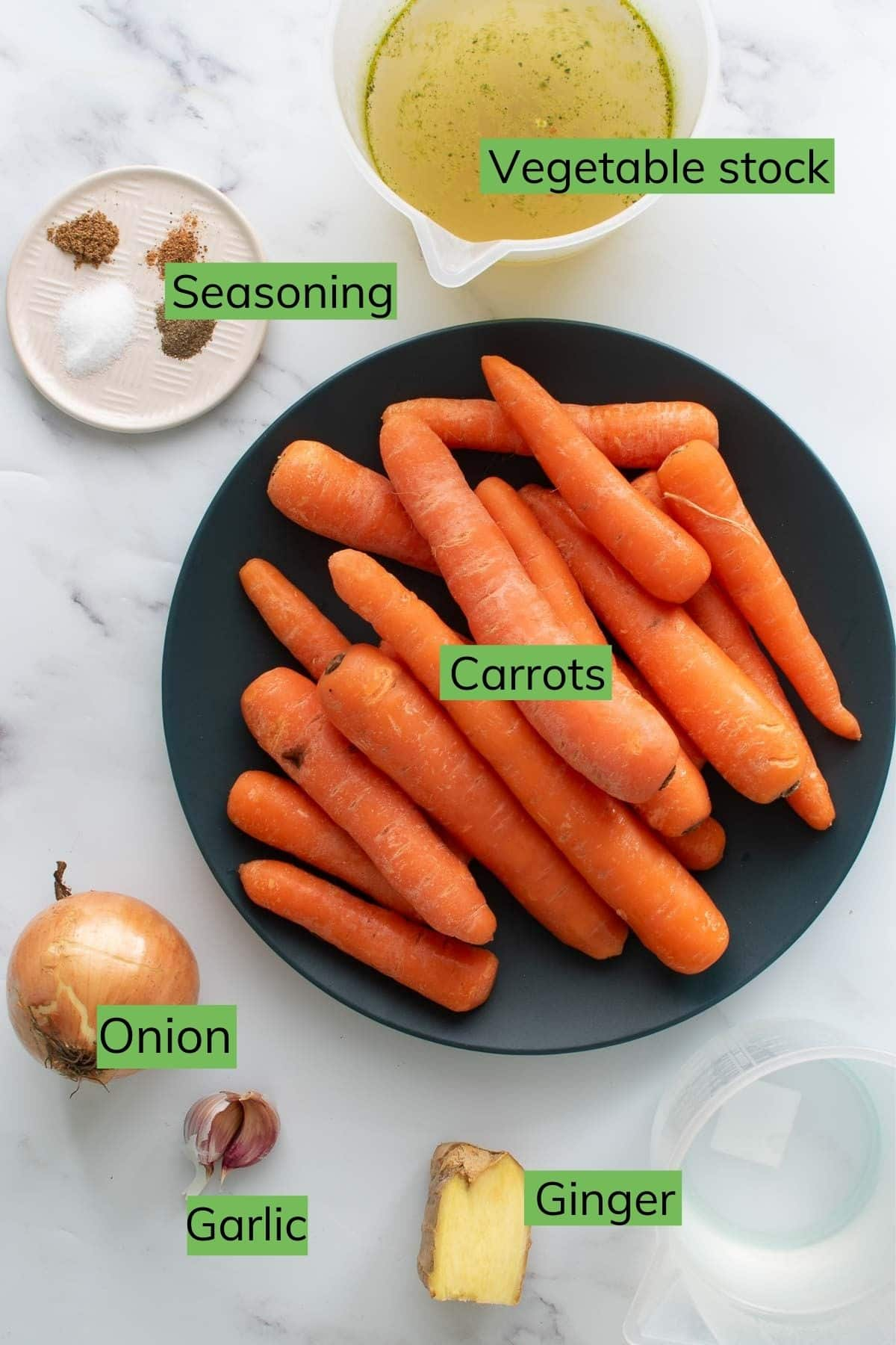 The ingredients needed to make carrot and ginger soup laid out on a table.