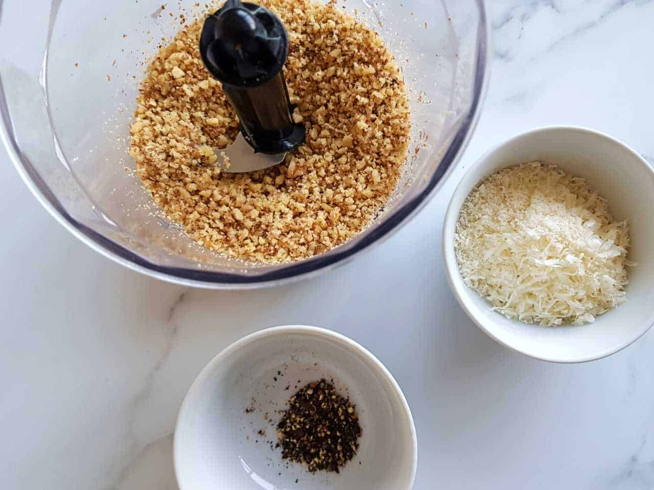 Ingredients for walnut crusted chicken in white bowls on a marble table.