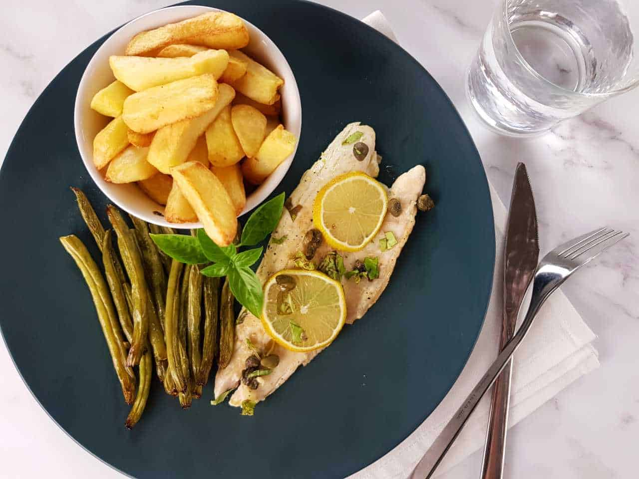 Pan seared sea bass with lemon and capers on a blue plate with chips and green beans on a marble table. Glass of water and cutlery on the side.