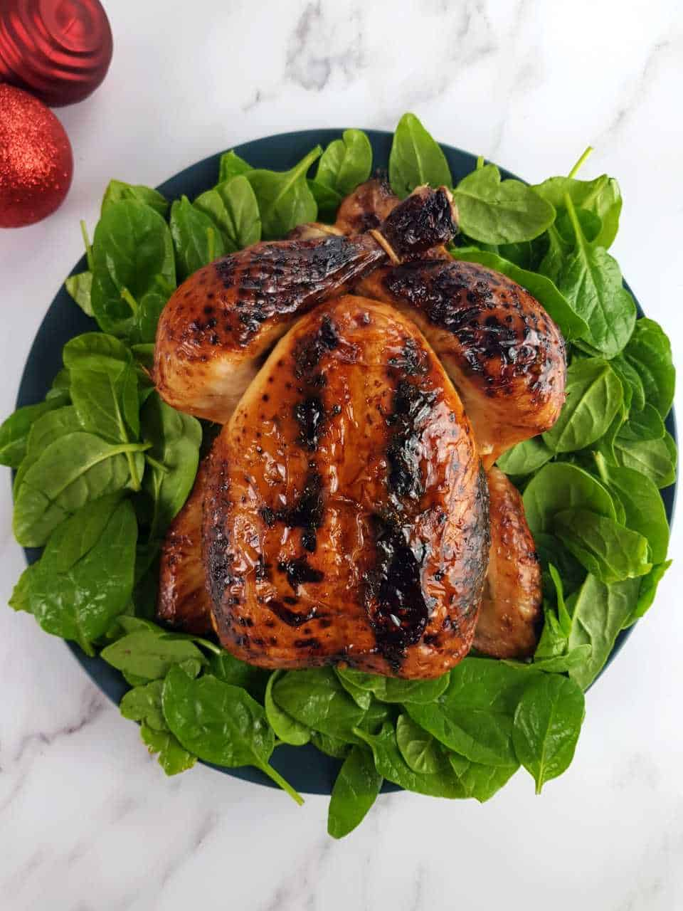 Roast chicken in honey on a bed of spinach on a marble table.