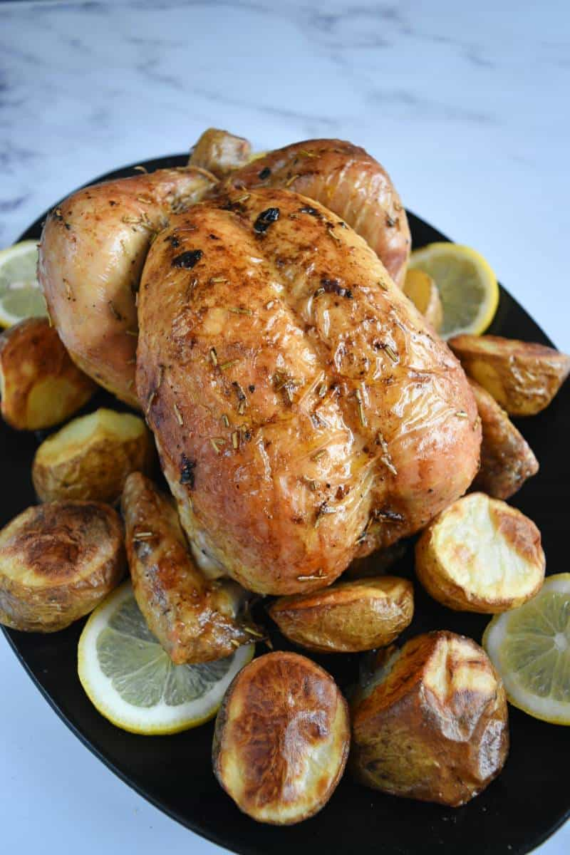 Roast chicken on a plate with lemon slices and potatoes.
